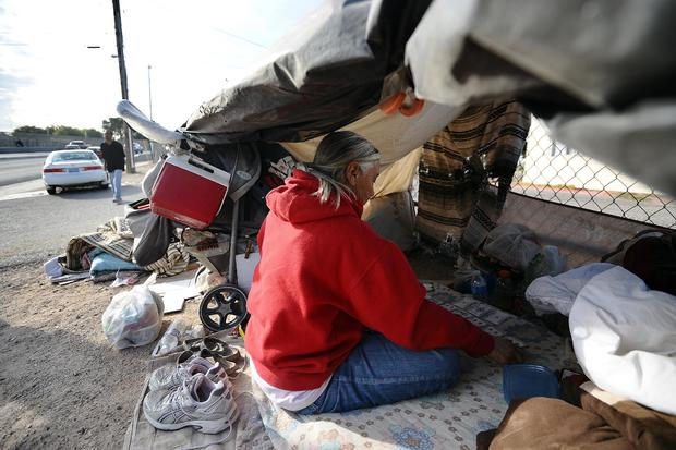 A homeless woman plays card in her tent