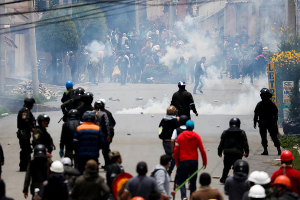 Supporters of Bolivian President Evo Morales and opposition supporters clash during a protest after Morales announced his resignation on Sunday, in La Paz