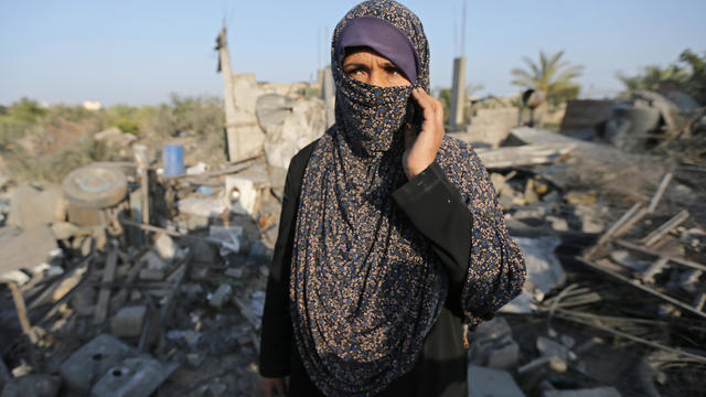 Palestinian woman looks on as she stands in front of a house destroyed in an Israeli air strike in the southern Gaza Strip