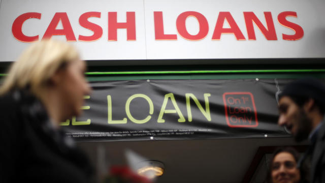 Pedestrians pass by a lending shop in northeast London