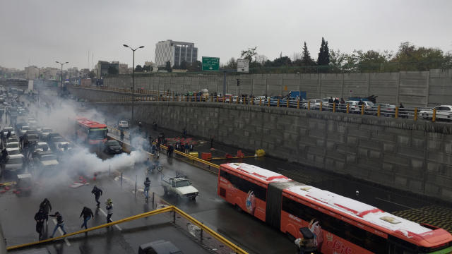 Riot police tries to disperse people as they protest on a highway against increased gas price in Tehran