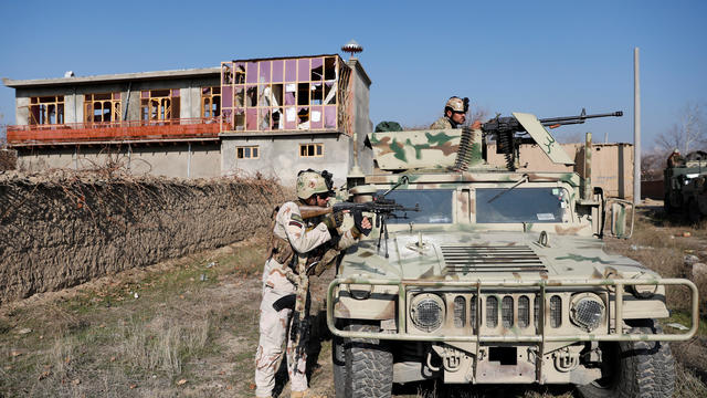 Afghan security forces take position at the site of an attack in a U.S. military air base in Bagram