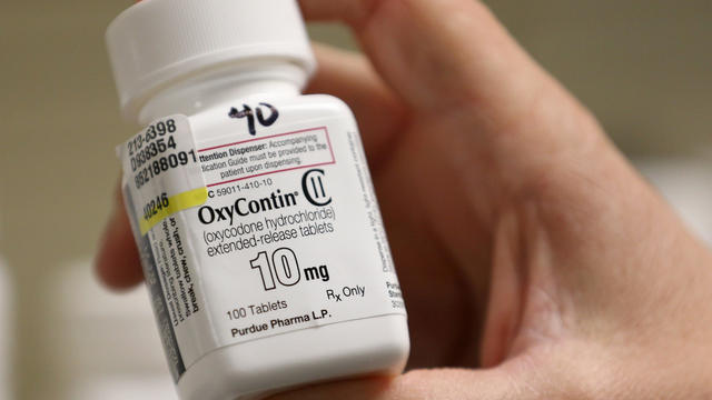 A pharmacist holds a bottle OxyContin made by Purdue Pharma at a pharmacy in Provo, Utah