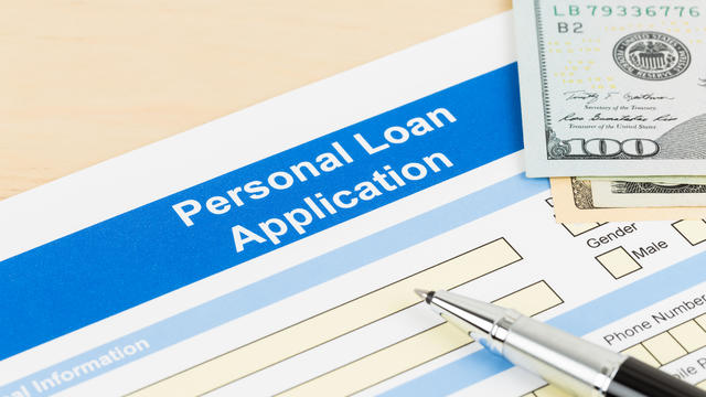 Personal loan application form with dollar money banknote, and pen