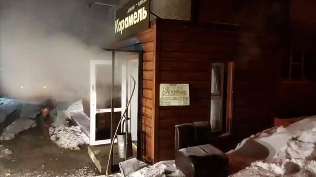 Steam comes out from a door of the Mini Hotel Caramel after a hot water pipe exploded in the night and flooded a basement hotel room with boiling water, in Perm