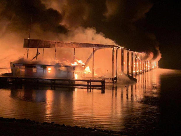 A row of boats is engulfed in flames after catching fire at a marina in Scottsboro, Alabama, January 27, 2020.