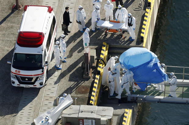 Officers in protective gear escort a person who was on board cruise ship Diamond Princess and was tested positive for coronavirus, after the person is transferred to a maritime police base in Yokohama