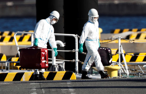 Officers in protective gears carry luggage cases after people who were transferred from cruise ship Diamond Princess, arrive at a maritime police's base in Yokohama