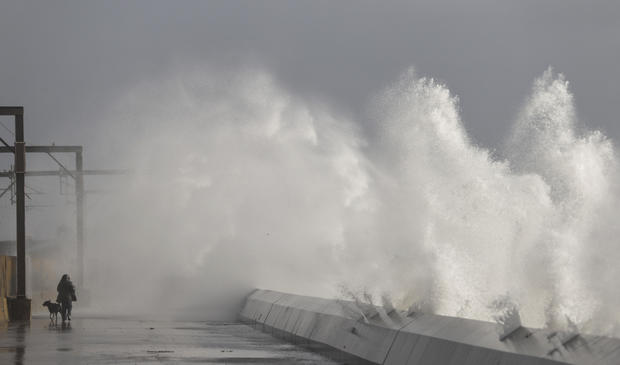 A man takes his dog for a walk as waves hit the sea wall in Saltcoats, Scotland