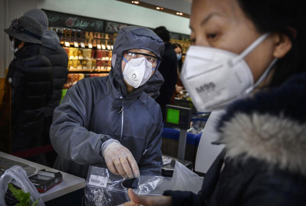 A Chinese worker wears a protective suit and mask as she scans groceries for a customer at a supermarket on February 11, 2020, in Beijing, China.