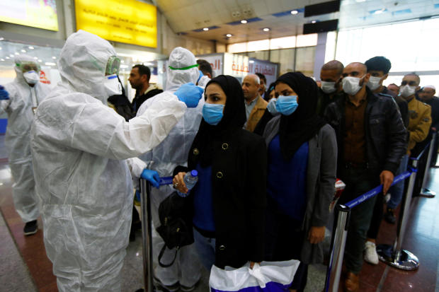 Iraqi medical staff check passengers' temperature upon their arrival at Najaf airport February 20, 2020.