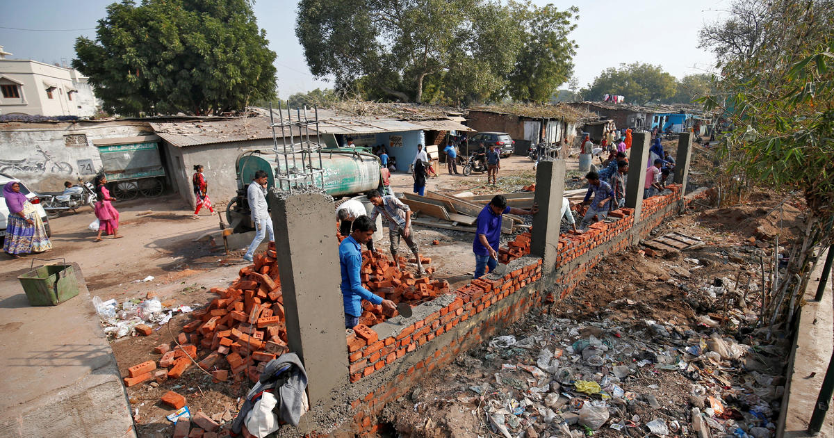 Before Trump visit, Indian city of Ahmedabad gets a facelift and a wall in front of a slum image
