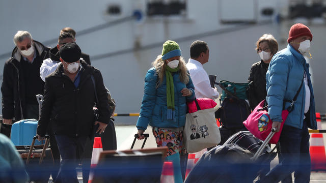 Passengers wearing masks leave cruise ship Diamond Princess at Daikoku Pier Cruise Terminal in Yokohama