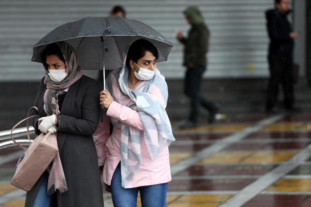Iranian women wear protective masks to prevent contracting coronavirus, as they walk in the street in Tehran