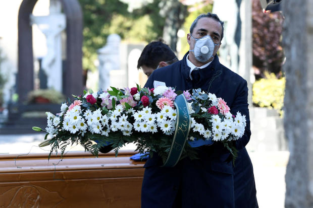 Cemetery workers and funeral agency workers in protective masks transport the coffin of a person who died from the coronavirus disease COVID-19 into a cemetery in Bergamo, Italy, March 16, 2020.