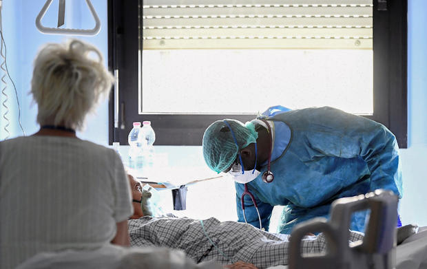 Medical worker wearing a protective mask, glasses and suit treats a patient suffering from coronavirus disease (COVID-19) in an intensive care unit at the Oglio Po hospital in Cremona
