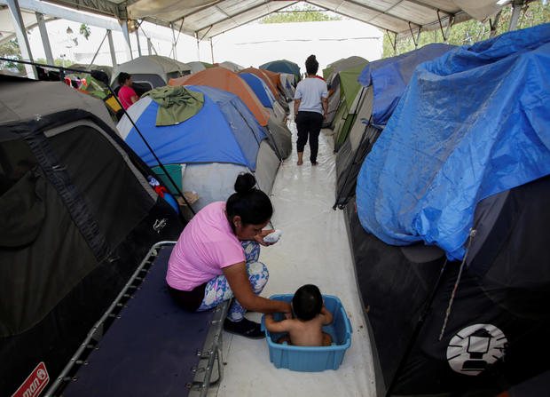 A migrant woman bathes her son outside their tent at a migrant encampment, where more than 2,000 people live while seeking asylum in the U.S, as the spread of the coronavirus disease (COVID-19) continues, in Matamoros