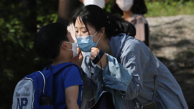 A mother kisses her child as they both wear masks to avoid the spread of the coronavirus disease (COVID-19) at an elementary school in Seoul