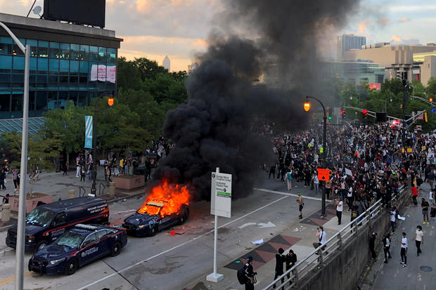 An Atlanta Police car burns as people protest near CNN Center in Atlanta