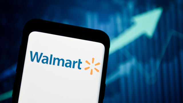 In this photo illustration a Walmart logo seen displayed on