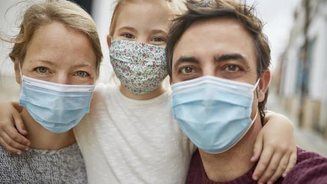 Optimistic Family Selfie during Coronavirus Emergency. All Wearing Protective Face Mask