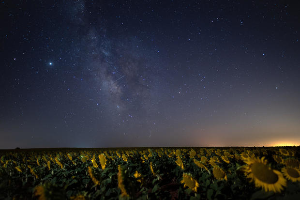 A meteor crossing the night sky over the Milky way in a