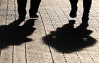 Two women walking down the street, black silhouettes and shadows on pavement