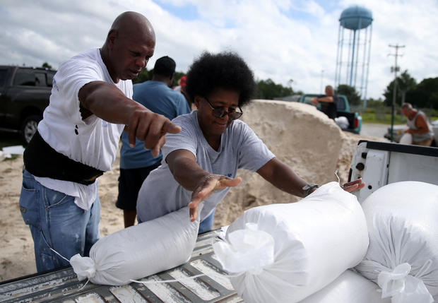 Sam Dorsey helps Dianne Fredrick load a sandbag in the back of her truck as Tropical Storm Sally approaches in Bay St. Louis