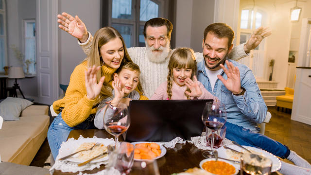 Beautiful family, sitting at the table with dinner meal, smiling, happy and using laptop. Family making videocall using laptop celebrating at home