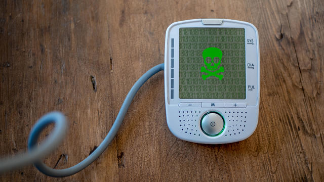 Medical device is hacked or infected by virus. Modern health care concept. Malware on blood pressure display.