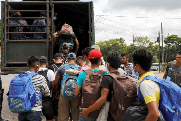 Honduran migrants trying to reach the U.S. get inside a truck escorted by the Guatemalan soldiers to send them back to Honduras, in Morales