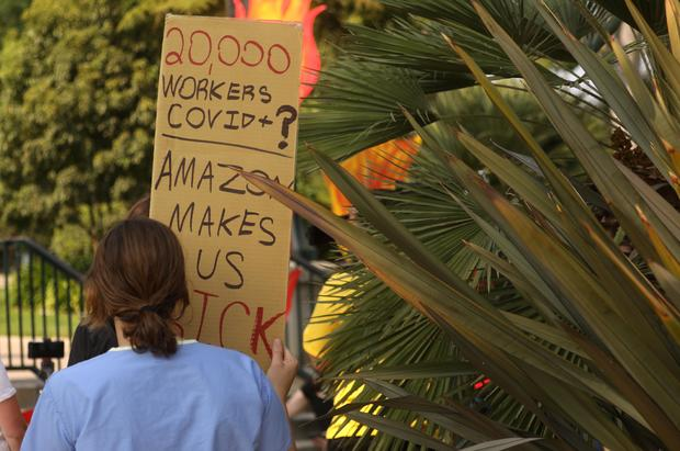 """Protester holds a sign reading, """"20,000 workers COVID+? Amazon makes us sick."""""""