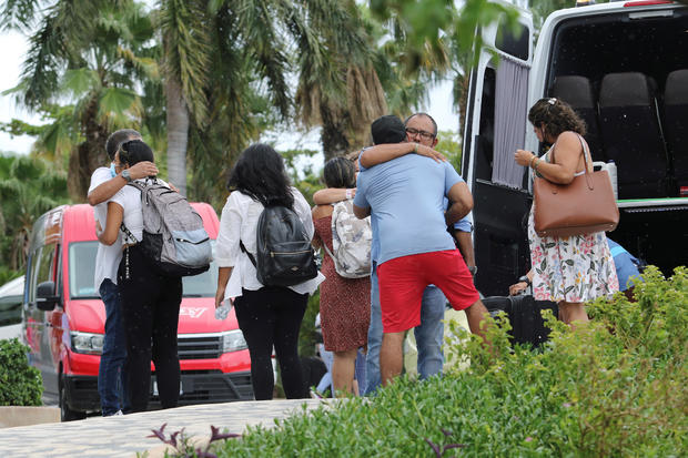 Tourists embrace as they leave a hotel ahead of the arrival of Hurricane Delta, in Cancun