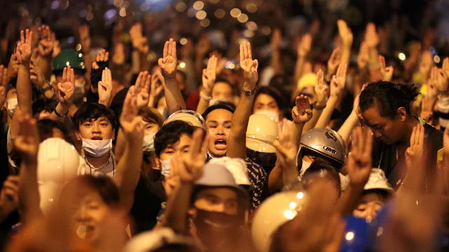 People show the three-fingered salute during a protest, in Bangkok