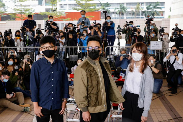 Pro-democracy activists Ivan Lam, Joshua Wong and Agnes Chow arrive at the West Kowloon Magistrates' Courts to face charges related to illegal assembly stemming from 2019, in Hong Kong