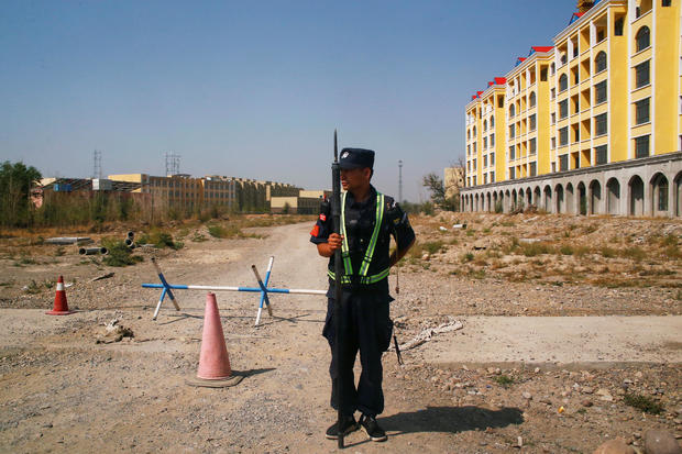 FILE PHOTO: A Chinese police officer takes his position by the road near what is officially called a vocational education centre in Yining