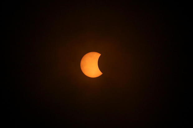 A solar eclipse is pictured during a cloudy day, in Villarrica