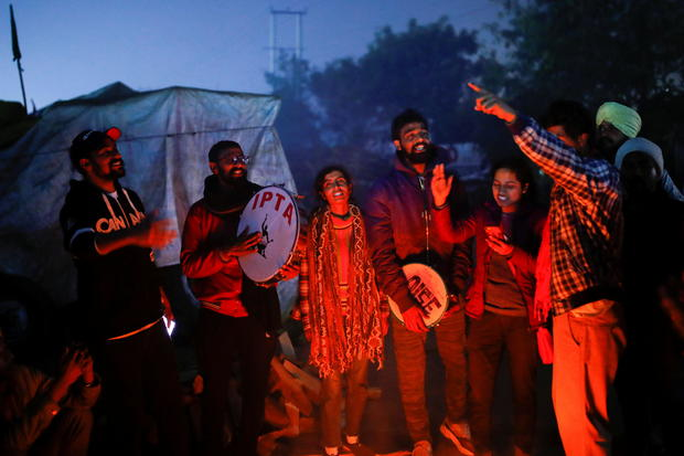 People sing as they gather to celebrate the arrival of the new year at the site of a protest against the newly passed farm bills at Singhu border near New Delhi