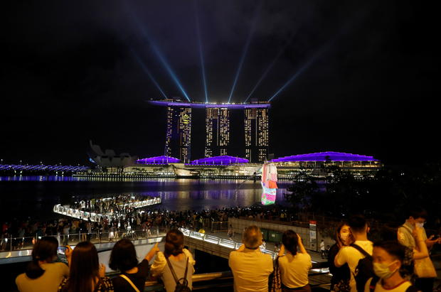 People watch a light show, as the traditional New Year's Eve fireworks are cancelled due to the coronavirus disease (COVID-19) outbreak, at Marina Bay in Singapore