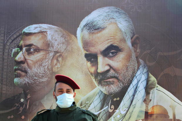 A member of Lebanon's Hezbollah stands in front of a picture depicting senior Iranian military commander General Qassem Soleimani and Iraqi militia commander Abu Mahdi al-Muhandis, during a ceremony marking the first anniversary of their killing, in Khiam