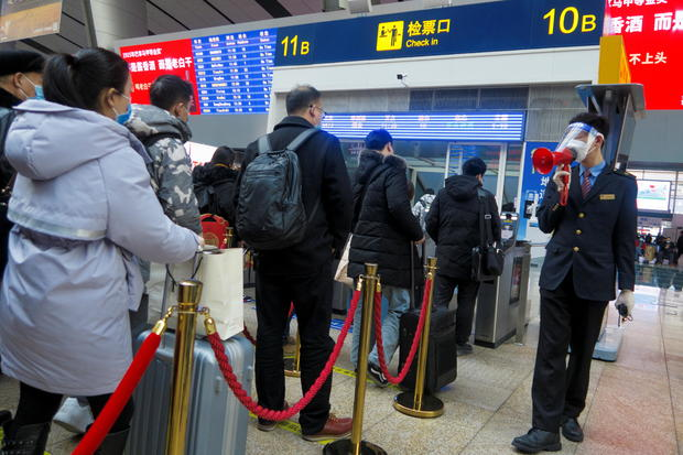 A station staff member speaks through a bullhorn to travellers waiting to board their train at Beijing South Railway station ahead of Lunar New Year celebrations following an outbreak of the coronavirus disease (COVID-19) in Beijing