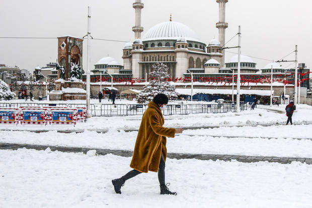 A woman walking along the snow-covered road in Istanbul