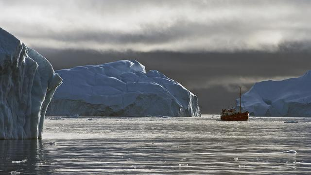Boat in the water near a Greenland iceberg