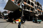 A boy walks past shops in Douma