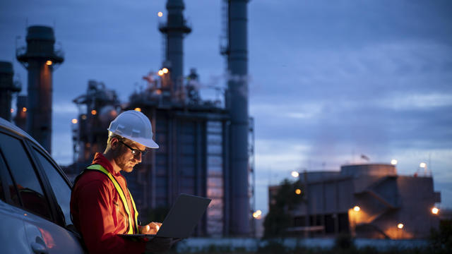 Petrochemical engineers work slowly and heavily with smart tablets in the oil and gas industry at night.