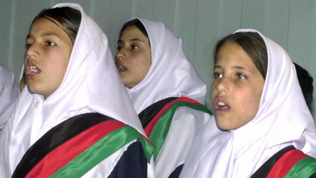 Afghan school children sing during a cer