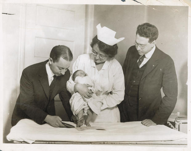 Nurse and Doctors During Footprinting of Newborn Baby