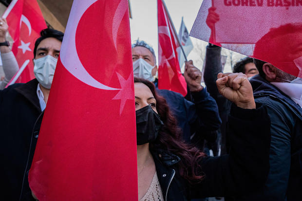 A protester makes a gesture while holding a Turkish flag in