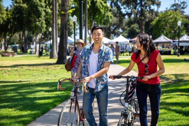 Los Angeles Couple Wheeling Bikes Through Park Durning Farmer's Market