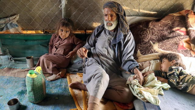 Ali al-Nehmi, 70, sits with his grandchildren in their hut at a camp for internally displaced people (IDPs) in Marib